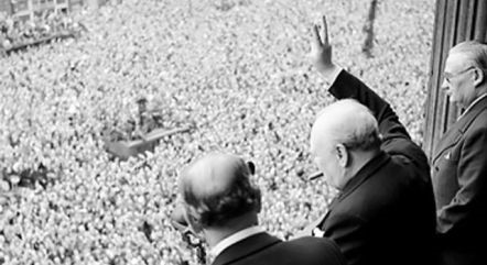 Victory in Europe in 1945 as people gather on the streets to celebrate. They are joined by Churchill who gives then the victory sign over a balcony.