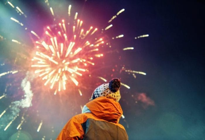 Small child watching the sky as it fills with fireworks.