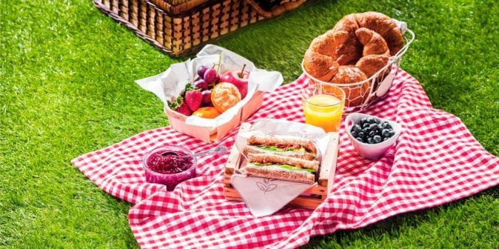 Lunchtime homemade picnic  for your VE Day celebrations. Consists of croissants, bowl of fruit, sandwiches and orange juice.