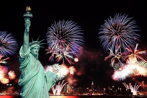 Independence Day blue, white and red fireworks behind the Stature of Liberty.